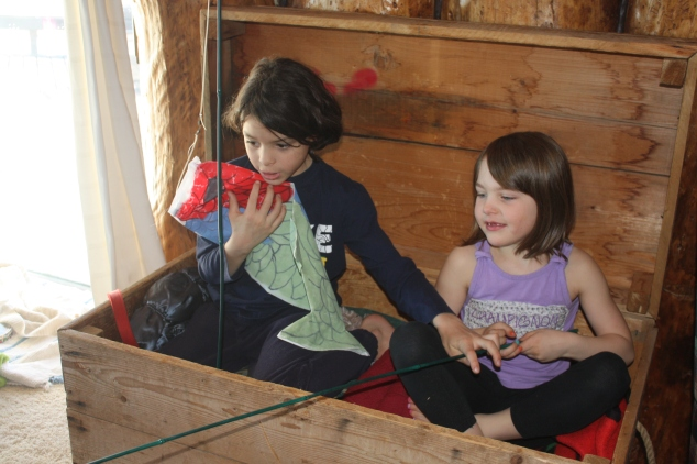 "When they decided to come inside they continued their adventure. They fished from their ""boat"" using their Japanese wind socks they made at the Fine Arts Centre. Zahra played the fish."
